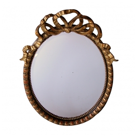 a festive and large-scaled napoleon iii ebonized and giltwood oval mirror with a carved ribbon crest