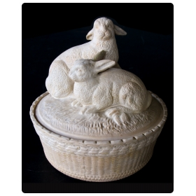 a charming french beige-colored pottery basket-weave bowl with cover adorned with two rabbits