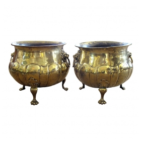 an exceptional and large-scaled pair of english hand-hammered brass lobed jardinières with lion ring handles
